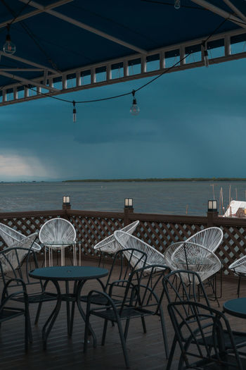 Empty chairs and tables in restaurant by sea against sky