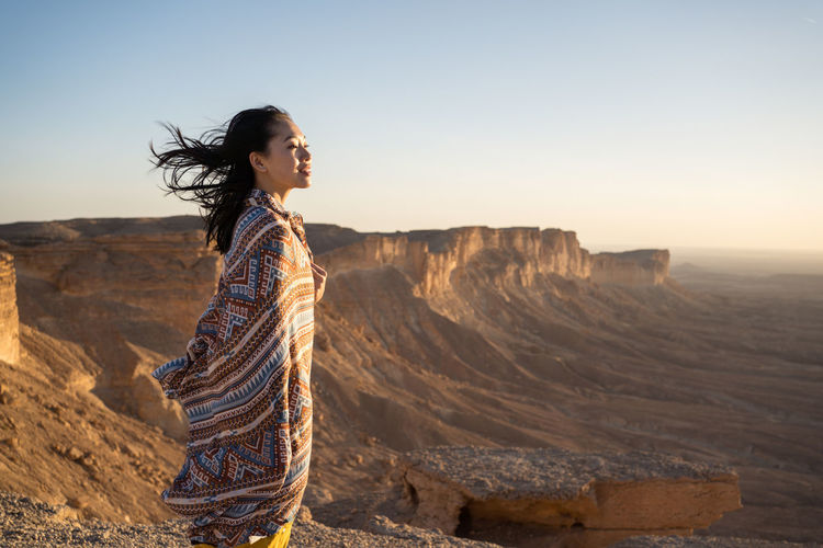 Side view of woman standing on rock against sky