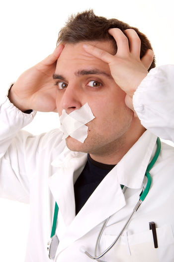 Close-up portrait of doctor with adhesive tape on mouth against white background
