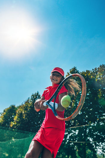 Low angle view of girl playing tennis