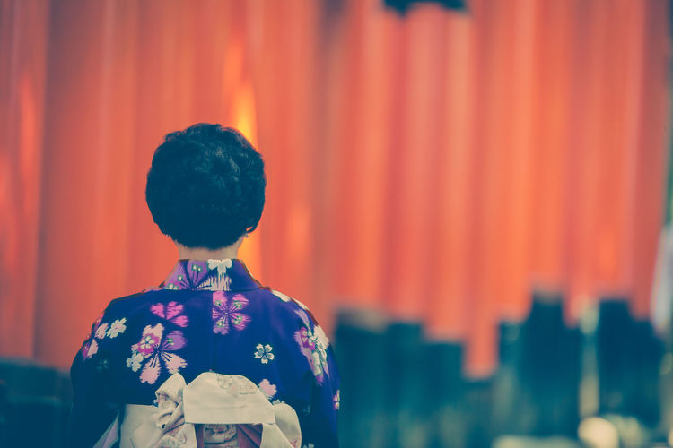 Rear View Of Woman Standing Against Torii Gates At Fushimi Inari Shrine