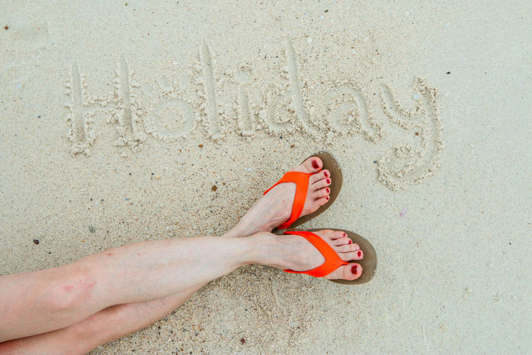 Low section of woman by holiday text on sand at beach