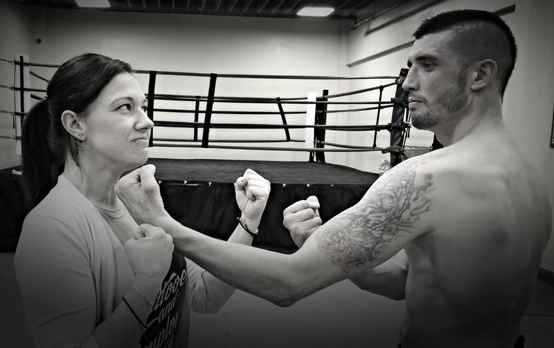 Couple gesturing while standing against boxing ring