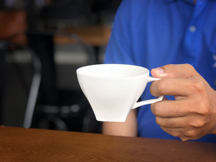 asian man catch hand holding a glass to drink more coffee in coffee shop Cup Mug Drink Coffee Cup Coffee Coffee - Drink Refreshment Holding Food And Drink Indoors  Cafe Real People Focus On Foreground Human Hand Hand One Person Midsection Men Hot Drink Coffee Shop Drinking Latte