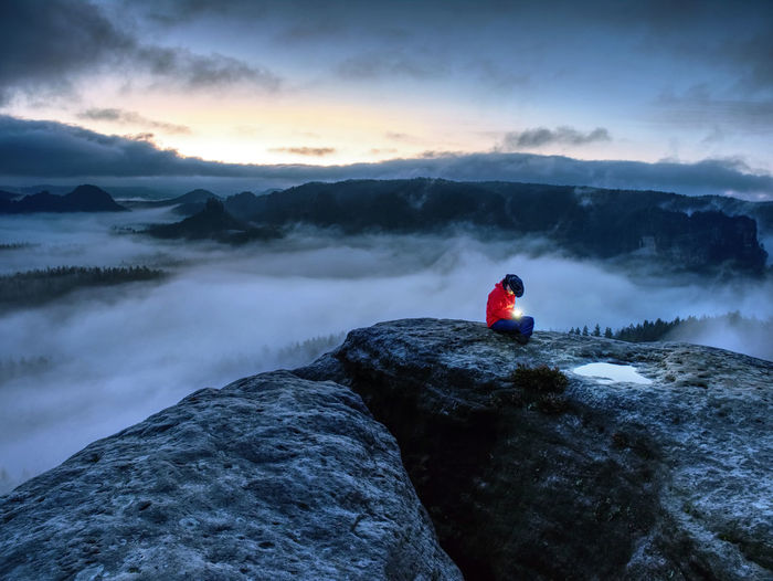Nice woman sit on summit in hands hold lamp. girl wait in misty darkness for sun in high mountains