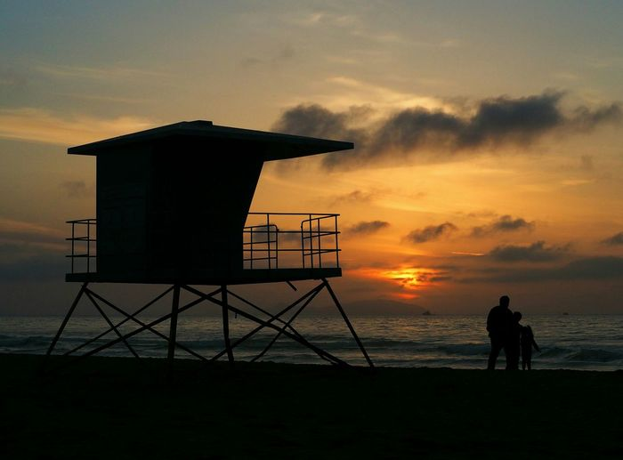 Silhouette people by lifeguard hut on beach against sky during sunset
