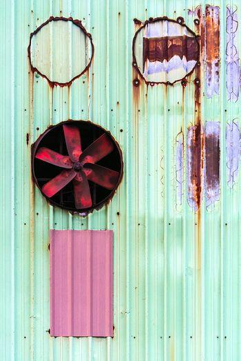 Exhaust fan on rusty metallic wall