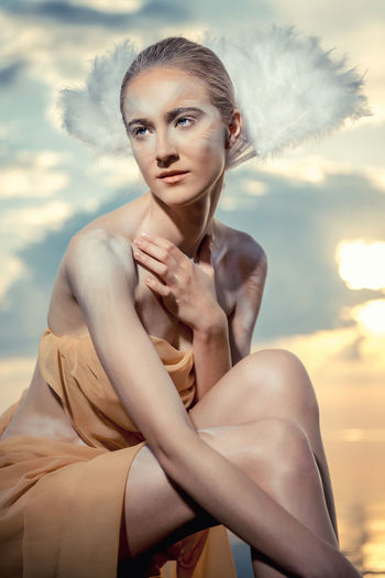 Portrait of young woman sitting against sky