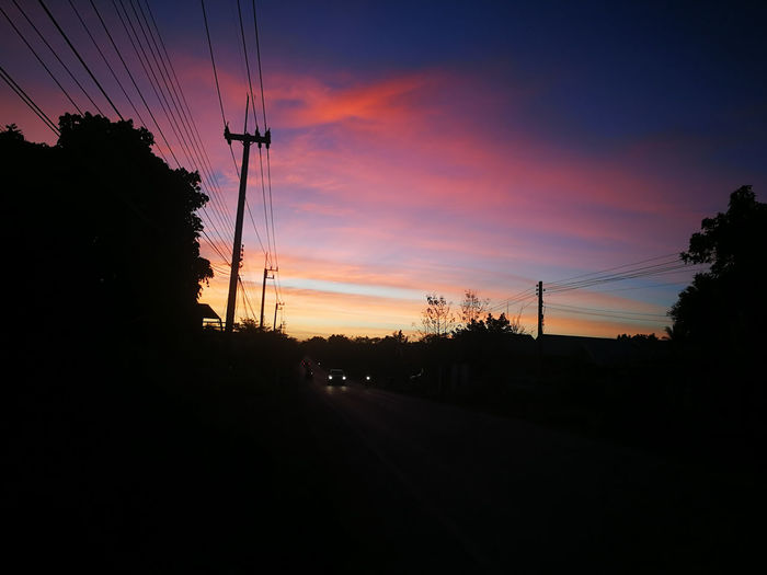 Silhouette trees and electricity pylon against sky during sunset