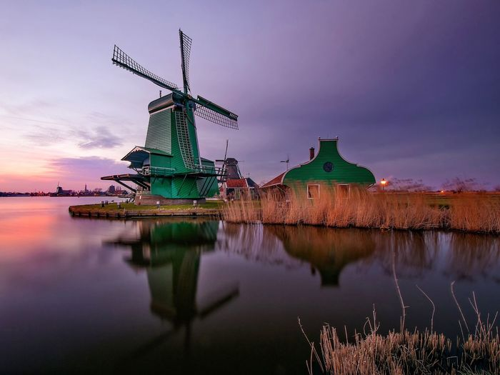 Windmill by calm lake against sky during sunset at zaanse schans