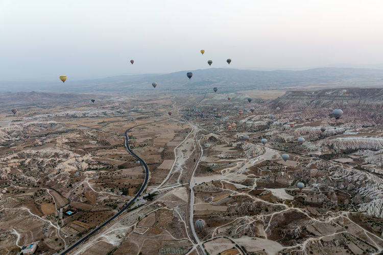Aerial view of hot air balloons flying over landscape