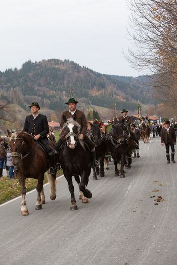 Schliersee, Bavaria - November 5, 2017: Every year on the 1st Sunday in November, the Idyllic Horse procession, named Leonhardi in Bavarian Schliersee takes place in commemoration of Patron St. Leonhard. In traditional clothing and decorated horse-drawn carriages horses and riders move to the church of St. Leonhard Bavaria Leonhard Ride Leonhardi Patron St. Leonhard Schliersee Traditional Clothing Adult Cart Day Domestic Animals Field Horse Horse Procession Horseback Riding Idyllic Livestock Mammal Men Nature Outdoors People Real People Sky Togetherness Tree