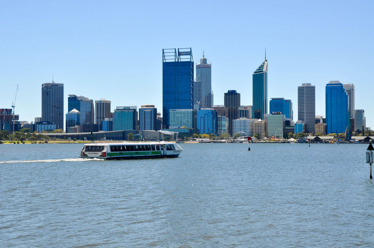 Transperth ferry crossing the Swan River with Perth's modern cityscape in Western Australia. Architecture Building Exterior Business Finance And Industry City Cityscape Clear Sky Ferry Ferry Harbor Modern Nautical Vessel Outdoors Passenger Craft Perth River Sky Skyscraper Transperth Transportation Travel Travel Destinations Urban Skyline Water Waterfront Western Australia