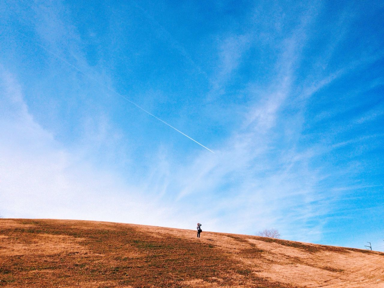 Person standing on arid landscape against cloudy sky