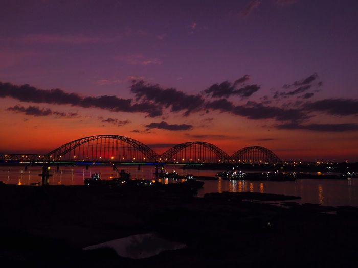 Silhouette bridge over illuminated city against sky at sunset