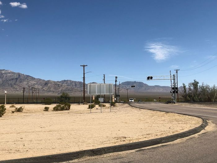 Mojave National Preserve Desert Landscape Roadside Railroad Crossing Sky Nature Day Sunlight No People Land Blue Outdoors Cloud - Sky Copy Space Sand Environment Fence Scenics - Nature