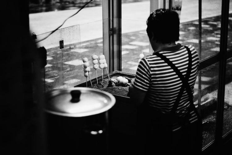 Rear View Of Person Cooking Food In Restaurant