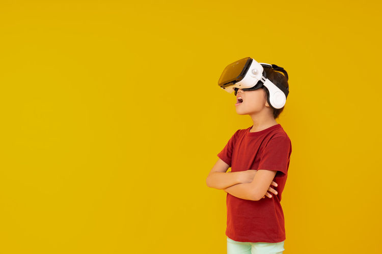 Boy wearing vr box standing against yellow background