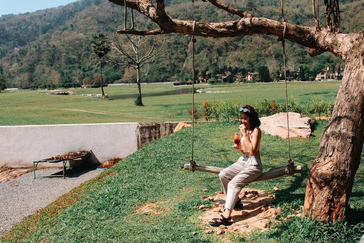Woman sitting on field by tree