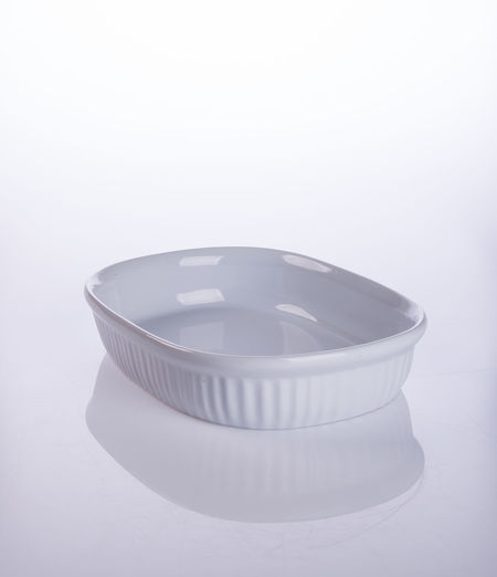 Close-up of empty casserole on table against white background
