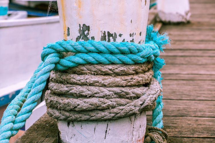 Close-up of rope tied on wooden bollard