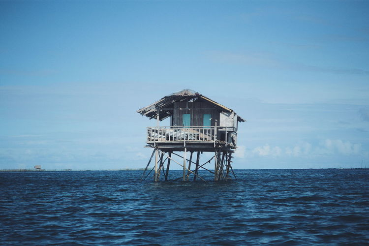 Abandoned stilt house in sea against sky