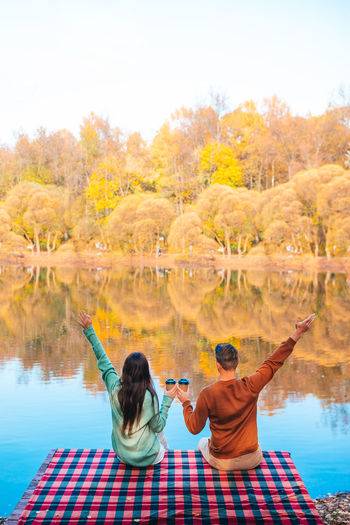 Rear view of people in lake during autumn