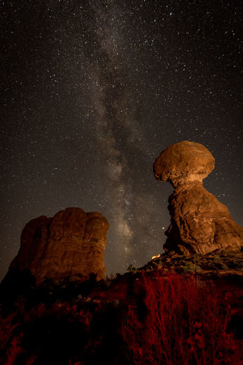 Low angle view of rock formation against sky at night