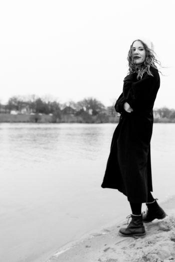 Full length portrait of woman standing against sky
