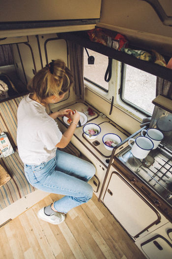 Preparing breakfast in a Volkswagen T3 Westfalia camper van. Vanlife is the best life. One Person Sitting Lifestyles Casual Clothing Women High Angle View Real People Young Women Kitchen Jeans Females Young Adult Indoors  Westfalia Campervan Camper Camping Cooking Tenerife Van Vanlife Homeonwheels Travel Travel Destinations Traveling