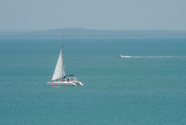 Darwin, Northern Territory, Australia-Sept. 9,2018: Nautical vessels, including sailing catamaran, in the blue Timor Sea off the coast of Darwin, Australia Nautical Vessel Water Transportation Mode Of Transportation Sea Sailing Travel Waterfront Nature Day Beauty In Nature Sailboat Scenics - Nature Yacht Outdoors Luxury Yachting Darwin Timor Sea Boat Transportation Journey Adventure Exploration White Sail Catamaran Lifestyles Recreation  Vacations Outdoor Pursuit Recreational Boat Blue Turquoise Colored Northern Territory Australia Mast Horizon Over Water Motion Horizon Sky Wake - Water Motorboat Two Relaxation Tourist Tourism Top End Travel Travel Destinations