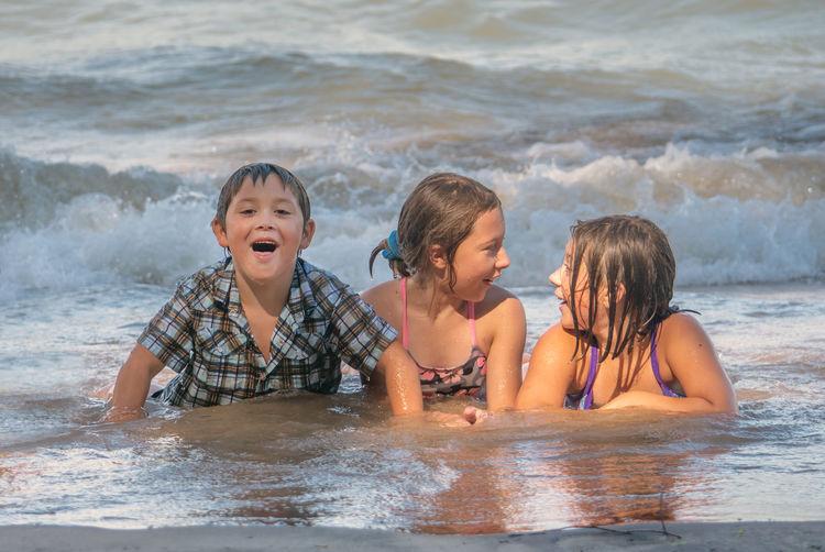 Happy friends on beach against sea