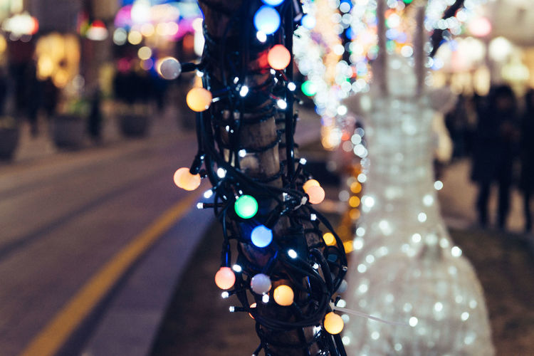 Illuminated Focus On Foreground Close-up Decoration City Street Incidental People Selective Focus Night Outdoors Defocused Transportation Lighting Equipment Multi Colored Holiday Road Art And Craft Lens Flare Human Representation