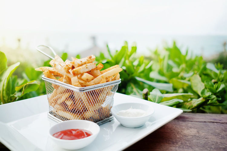 French Potato Fries on Metal Mesh Flying Sieve with Two Dipping Sauce, Served on Rustic Wooden Table in Outdoor French Fries Food Sauce Dish Plate Meal Snack Tomato Ketchup Restaurant Cafe Fast Background Mayonnaise Calories Junk Fresh Yellow Wooden Fat Table Flying Sieve  Lunch Unhealthy Fried Potato Chips Eat Crispy Modern Delicious Tasty Outdoor View Copy Space Photo Nobody Freshness Bowl Close-up Still Life