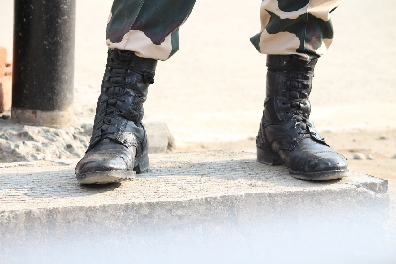 low section, human leg, shoe, body part, human body part, real people, day, standing, lifestyles, people, men, outdoors, boot, togetherness, two people, city, leisure activity, women, nature, human foot, human limb, jeans, uniform, leather