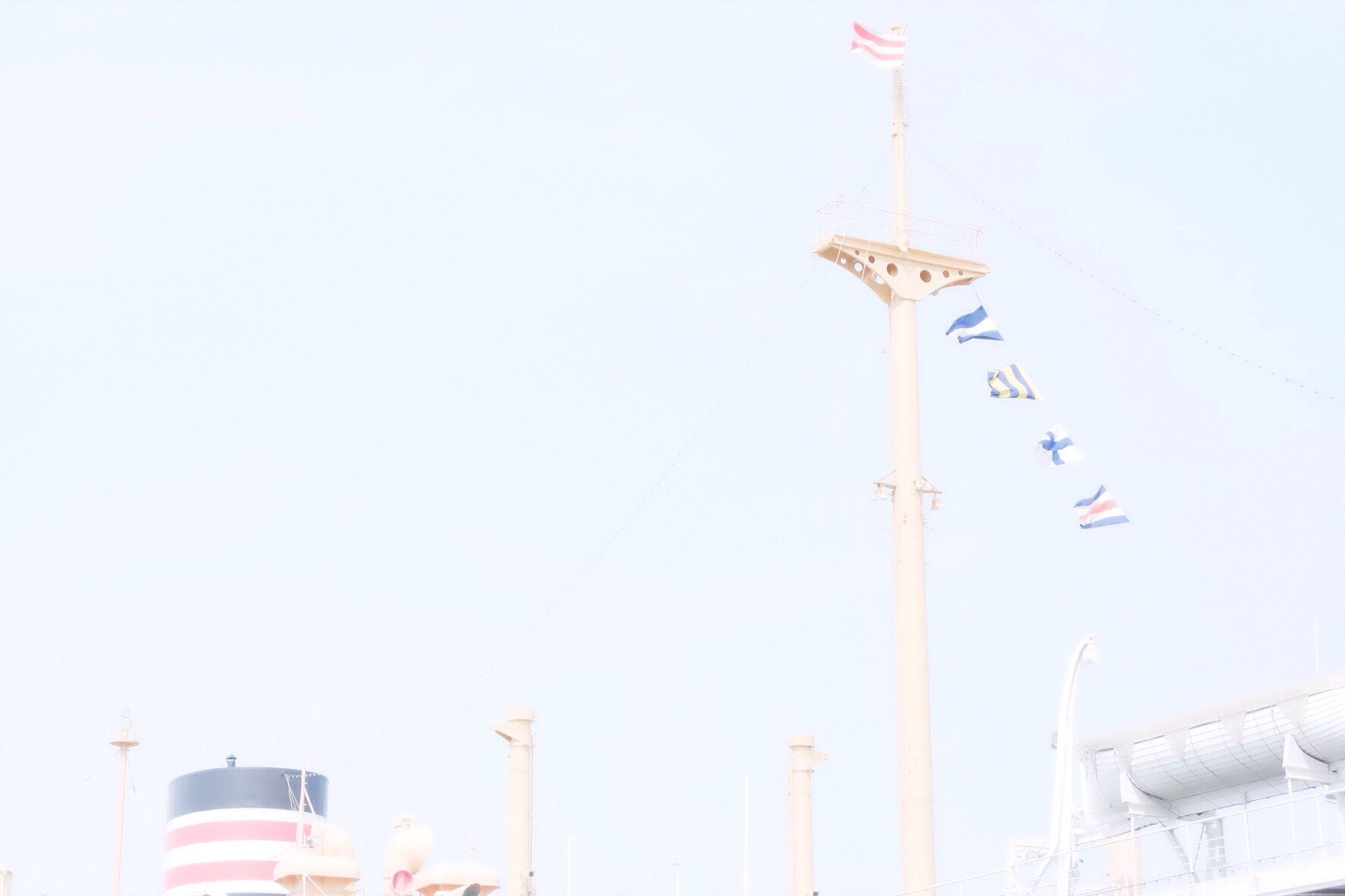 low angle view, clear sky, copy space, flag, built structure, architecture, national flag, tourism, travel, identity, travel destinations, famous place, international landmark, patriotism, communication, building exterior, tall - high, day, tower, capital cities