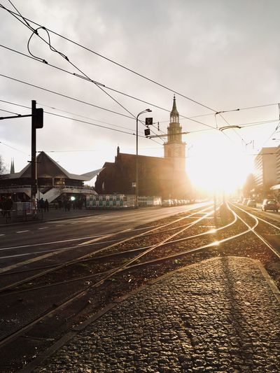 Railroad tracks by city against sky during sunset