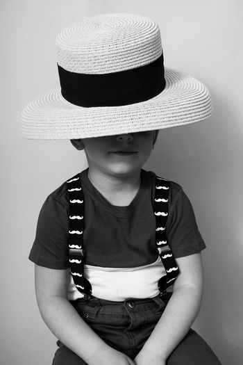 Girl wearing hat standing against white background