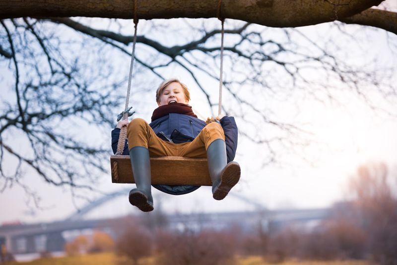 Full length portrait of boy swinging on rope swing