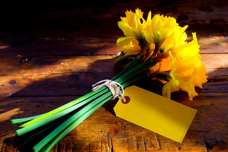 Celebration Romantic Yellow Flower Blank Label Blank Labels Bouquet Built Structure Close-up Daffodil Daffodils Flowers Day Easter Fire Flower Flower Head Fragility Freshness High Angle View Indoors  Nature No People Paper Table Text Space Wood - Material Yellow