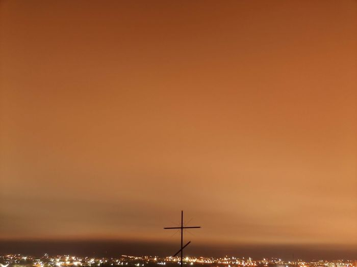 Silhouette of wind turbines against orange sky