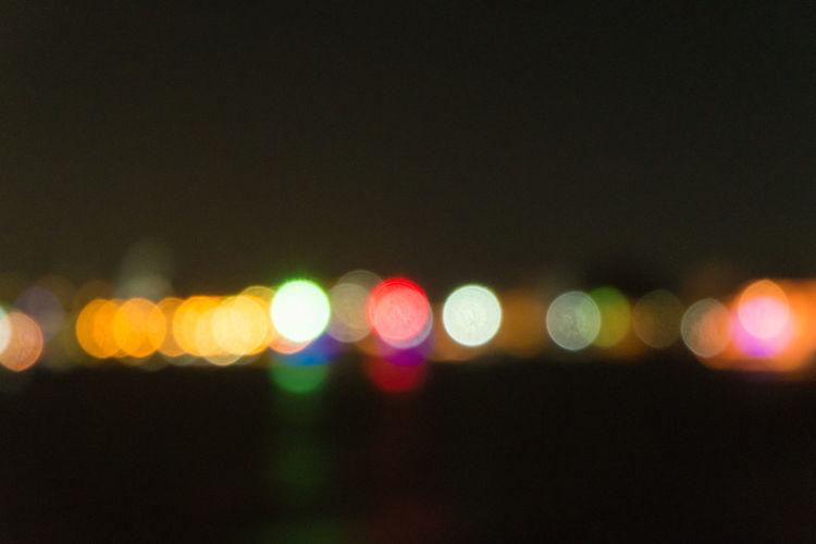 Defocused lights against sky at night