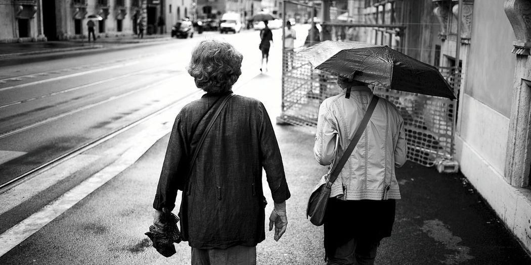 Rear View Of People Walking On Footpath In Rainy Season