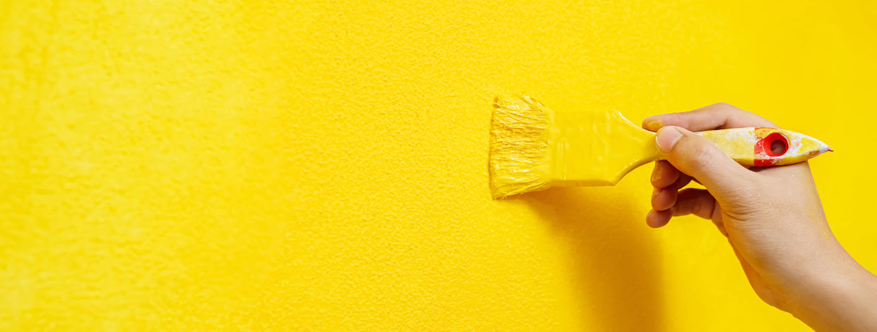 Close-up of hand holding yellow wall