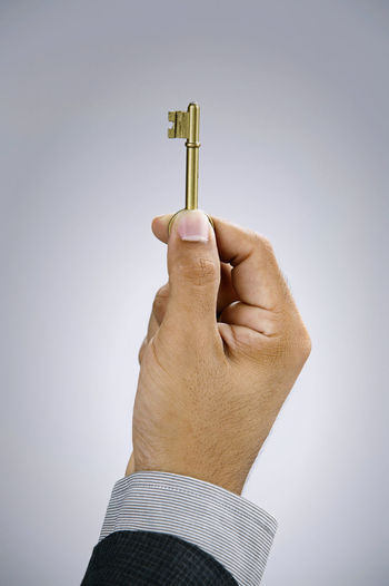 businessman holding a key Business Golden Adult Close-up Copy Space Financial Finger Hand Holding House Key House Keys Human Body Part Human Hand Indoors  Insurance Key Key Of Success Men One Person Opening Studio Shot Unlock White Background