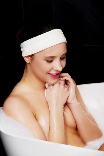 Smiling Woman Sitting In Bathtub