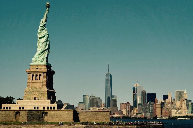 Statue Of Liberty And Cityscape Against Clear Sky