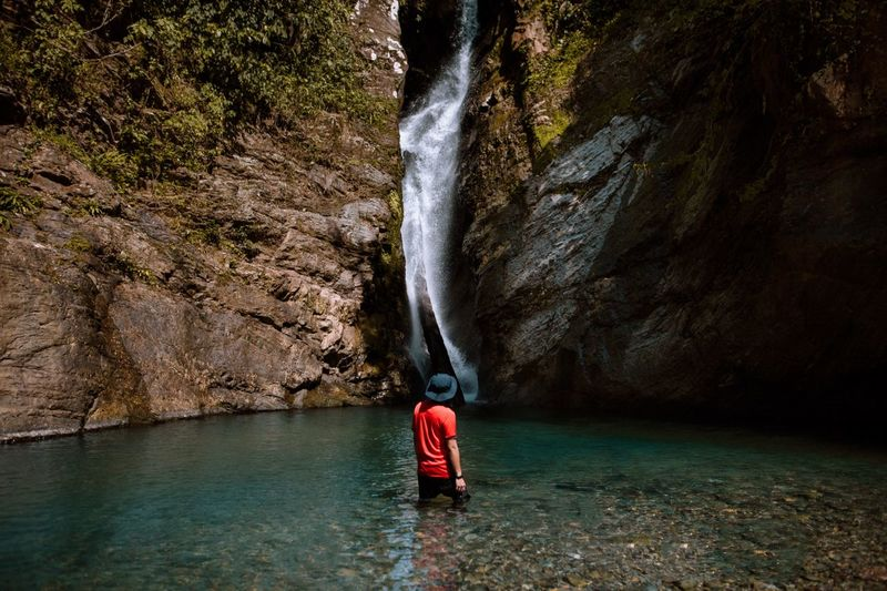 Rear view of man standing in lake against waterfall