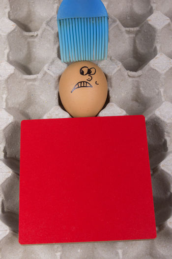 Cartoon face expression at egg and red board with finger also plastic brush Angry; Anthropomorphic Face Blue Brush; Blue Plastic Brush; Brush; Close-up Confuse; Egg Excited; Expression; Indoors  Joke; No People Plastic; Sad; Scare; Shy; Sick Text