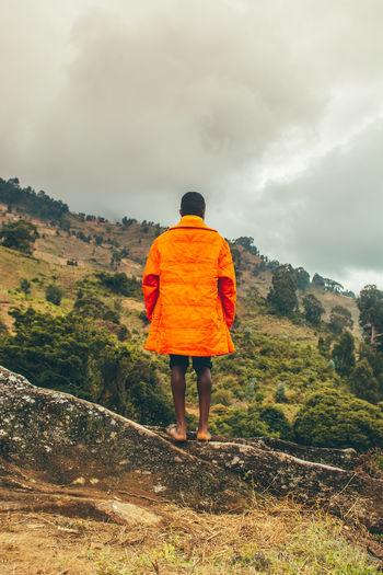 Rear view of man walking on mountain road